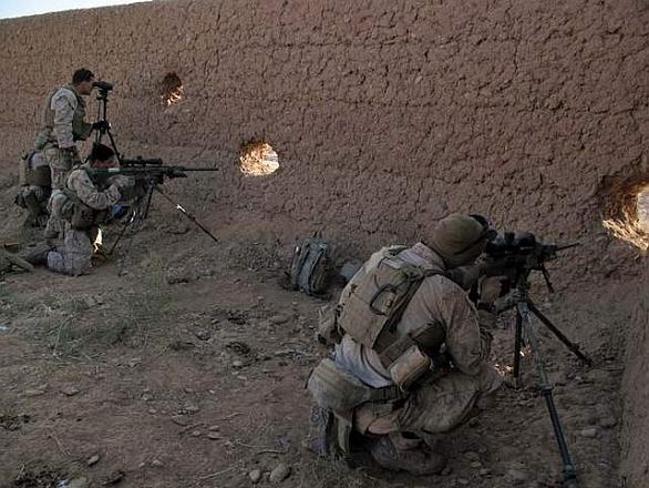 Američtí mariňáci pozorují okolí skrz otvory ve zdi kalátu. Kalát je typická forma afghánského obydlí. Jedná se o dům s dvorem obehnaným vysokou hliněnou zdí, která dříve sloužila k obranným účelům. Otvory však neslouží jen mariňákům, ale i povstalcům. / U.S. Marine Corps