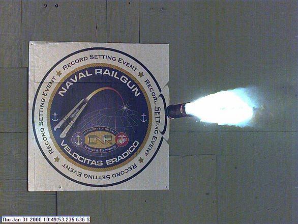 Foto: Testovací projektil vystřelený z EM kanónu. Všimněte si ionizovaného vzduchu za projektilem a také stlačeného vzduchu před projektilem. / US Navy